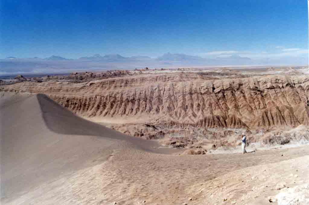 """Valle de la Luna bei San Pedro de Atacama: Geologisch gesehen befindet man sich im """"Tal des Mondes"""" auf dem Grund eines durch Gebirgsfaltung verschwundenen Sees. Man glaubt sich in eine Mondlandschaft versetzt beim Anblick der Szenerie aus bizarren Salzgebilden und Felsformationen, die besonders im frühen Morgenlicht und in der späten Nachmittagssonne in allen möglichen Farben glitzern. Hinzu kommen riesige Sanddünen wie in der Sahara."""